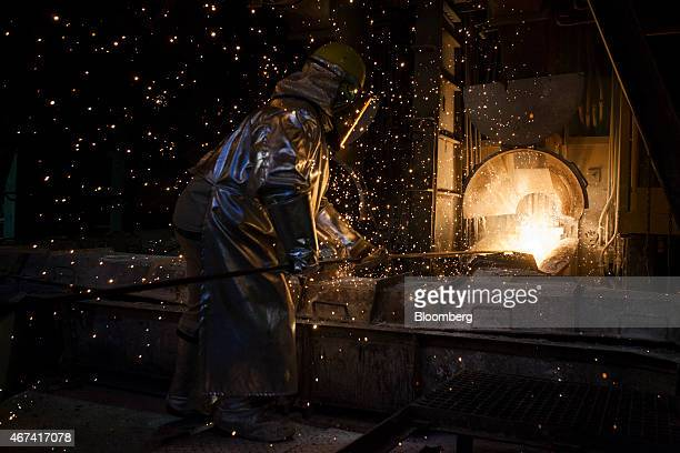 Sparks fly as a worker wearing heat resistant clothing opens a hot furnace at the KHGM Polska Miedz SA copper smelting plant in Glogow Poland on...
