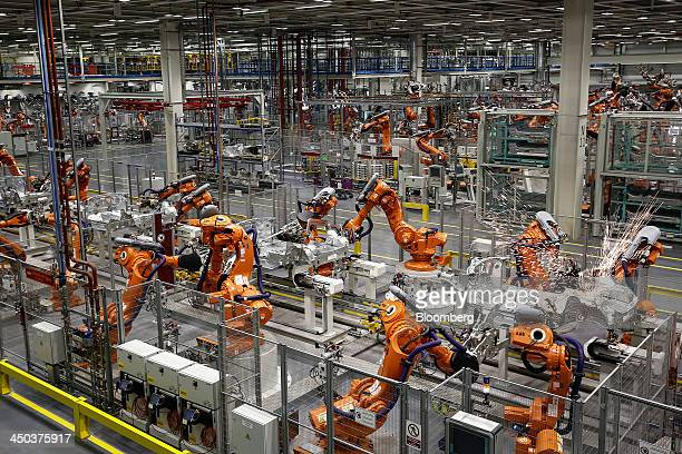 Sparks fly as ABB Ltd automated robots work on Mini automobile parts produced by Bayerische Motoren Werke AG as they move along the production line...