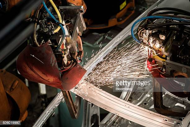 Sparks fly as an automobile chassis is welded by robotic arms inside the Mercedes-Benz AG automobile plant, operated by Daimler AG, in Kecskemet,...
