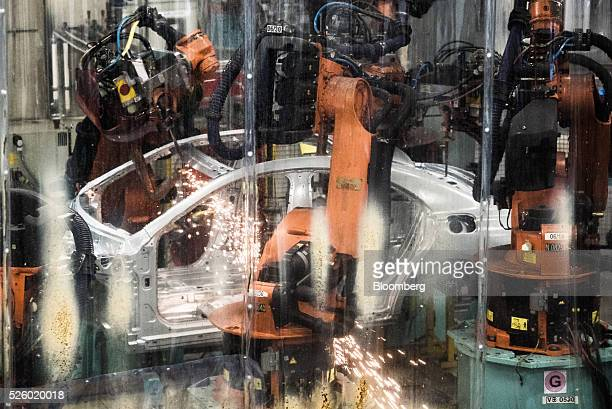 Sparks fly as an automobile chassis is welded on the production line inside the MercedesBenz AG automobile plant operated by Daimler AG in Kecskemet...