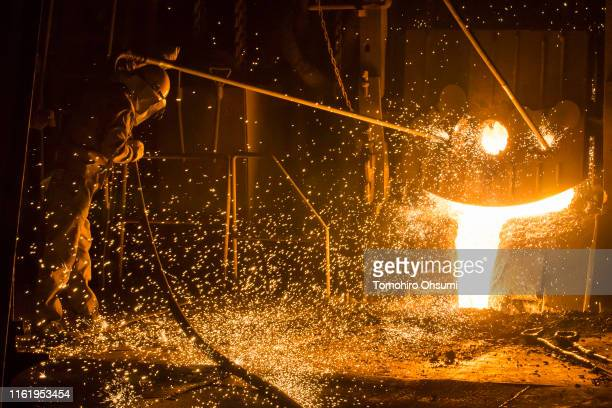 Sparks fly as an employee inspects molten steel from an electric arc furnace on the production line of the Jonan Steel Corp factory on July 14 2019...