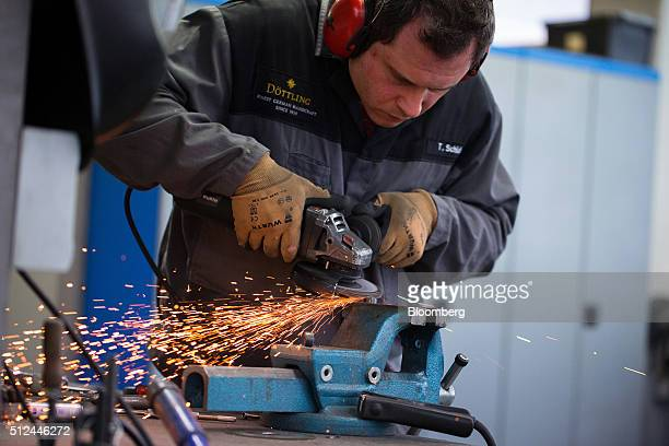 Sparks fly as an employee uses an angle grinder during luxury security safe manufacture in a workshop at the headquarters of Doettling GmbH in...