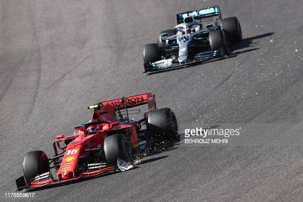 Sparks fly as Ferrari's Monegasque driver Charles Leclerc leads Mercedes' British driver Lewis Hamilton into a turn during the Formula One Japanese...