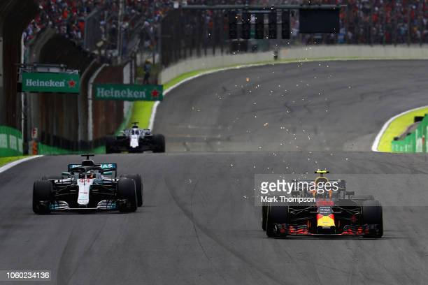 Sparks fly as Max Verstappen of the Netherlands driving the Aston Martin Red Bull Racing RB14 TAG Heuer overtakes Lewis Hamilton of Great Britain...