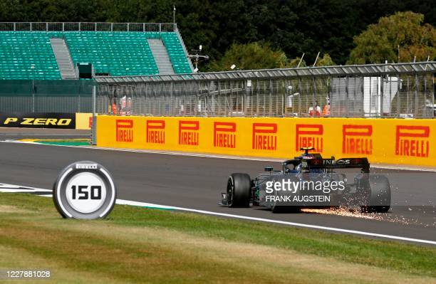 Sparks fly as Mercedes' Finnish driver Valtteri Bottas suffers a puncture during the Formula One British Grand Prix at the Silverstone motor racing...