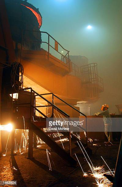 Sparks fly as molten steel flows from a ladle into casts at the TAMCO steel mini mill on October 4 2002 in Rancho Cucamonga California TAMCO...