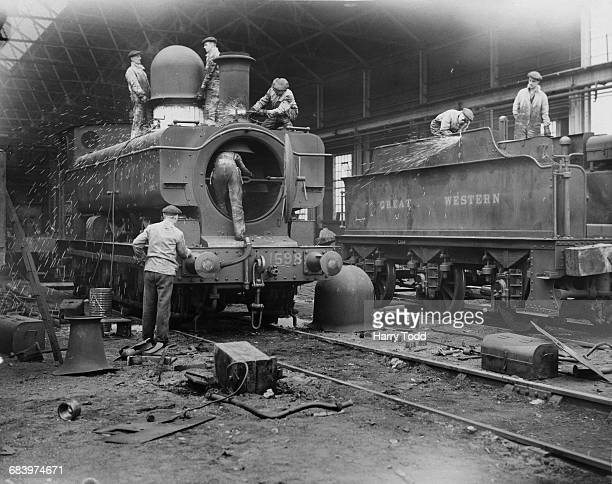 Sparks fly as rail workers using oxyacetylene torches start cutting and breaking down older Great Western Railway GWR 1076 Class steam locomotives at...
