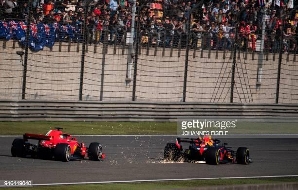 TOPSHOT Sparks fly as Red Bull's Australian driver Daniel Ricciardo overtakes Ferrari's German driver Sebastian Vettel during the Formula One Chinese...