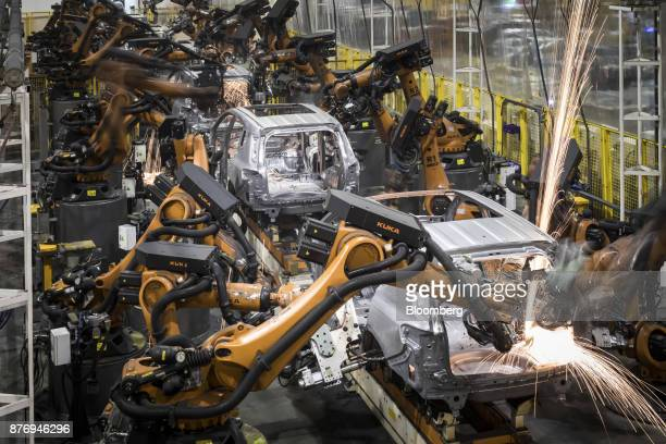 Sparks fly as robotic arms manufactured by Kuka AG work on the chassis of Trumpchi brand vehicles on a production line at the Guangzhou Automobile...