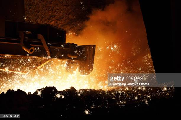 Sparks fly as the core of the blast furnace is opened at a steel plant