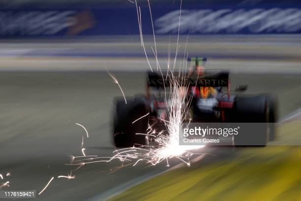 Sparks fly behind Alexander Albon of Thailand driving the Aston Martin Red Bull Racing RB15 on track during qualifying for the F1 Grand Prix of...