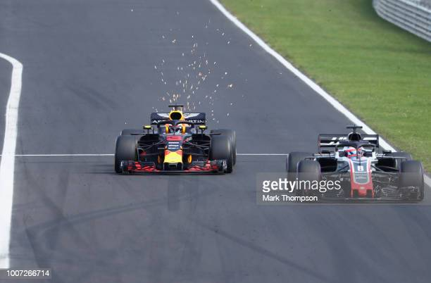 Sparks fly behind Daniel Ricciardo of Australia driving the Aston Martin Red Bull Racing RB14 TAG Heuer as he overtakes Romain Grosjean of France...