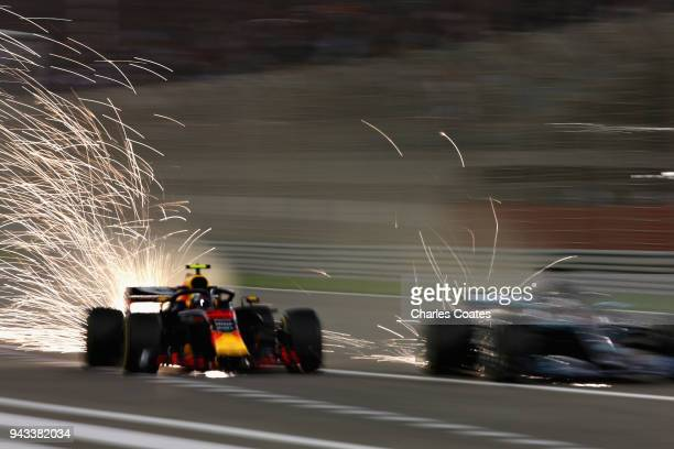 Sparks fly behind Max Verstappen of the Netherlands driving the Aston Martin Red Bull Racing RB14 TAG Heuer and Lewis Hamilton of Great Britain...