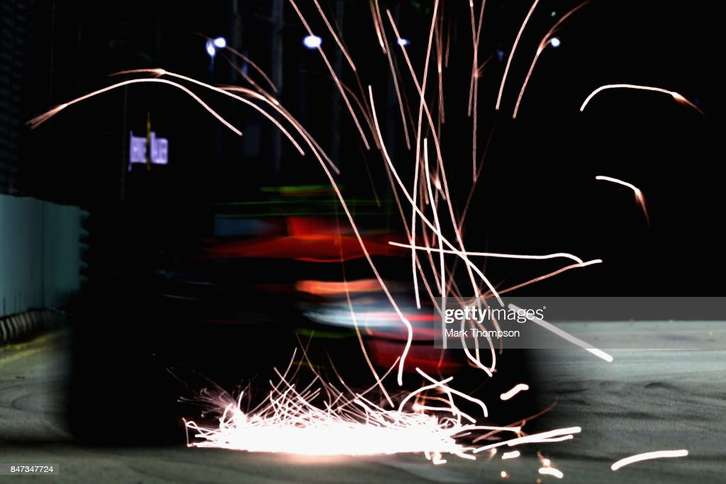 Sparks fly behind Max Verstappen of the Netherlands driving the (33) Red Bull Racing Red Bull-TAG Heuer RB13 TAG Heuer on track during practice for the Formula One Grand Prix of Singapore at Marina Bay Street Circuit on September 15, 2017 in Singapore.