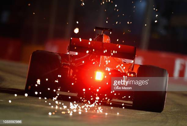Sparks fly behind Sebastian Vettel of Germany driving the Scuderia Ferrari SF71H on track during qualifying for the Formula One Grand Prix of...