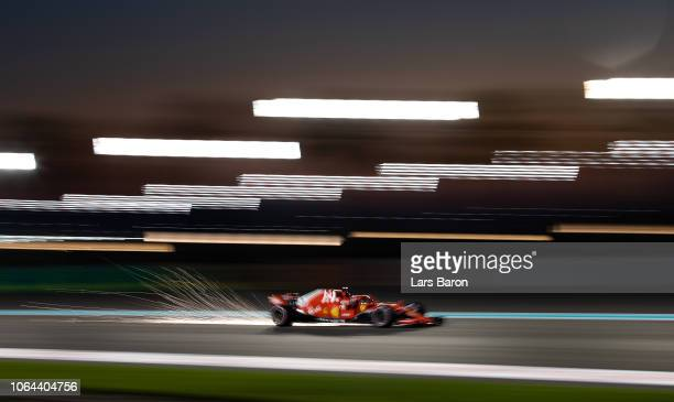 Sparks fly behind Sebastian Vettel of Germany driving the Scuderia Ferrari SF71H on track during practice for the Abu Dhabi Formula One Grand Prix at...