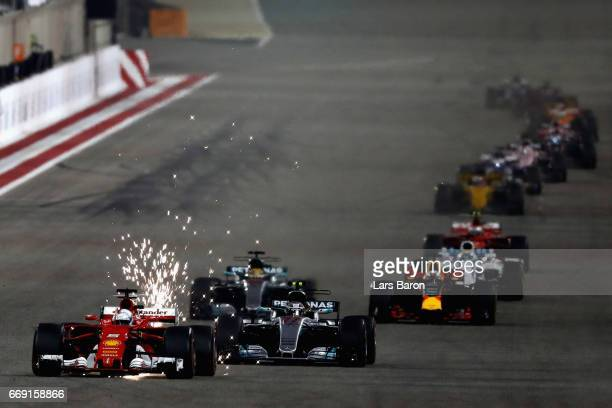 Sparks fly behind Sebastian Vettel of Germany driving the Scuderia Ferrari SF70H ahead of Valtteri Bottas driving the Mercedes AMG Petronas F1 Team...