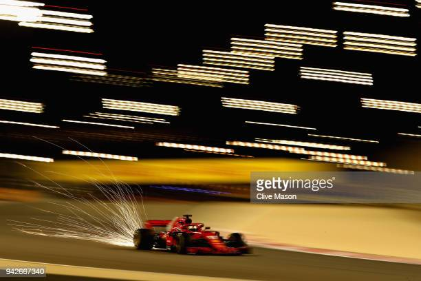 Sparks fly behind Sebastian Vettel of Germany driving the Scuderia Ferrari SF71H on track during practice for the Bahrain Formula One Grand Prix at...