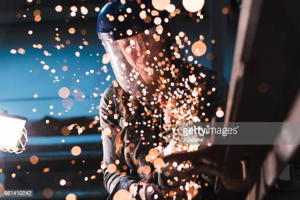 Sparks flying towards lens as a woman uses an angle grinder