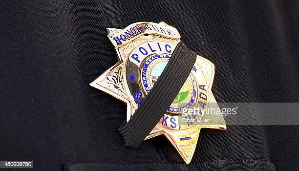 Sparks Police Department Lt and honor guard coordinator Pete Krall wears a badge with a black ribbon across it as he waits for the start of the...