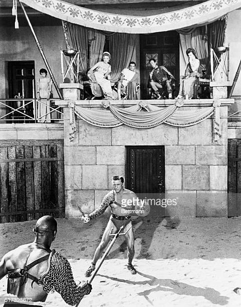 Spartacus battles with Draba as his wife Varinia , watches in the balcony with members of the Roman royalty : Helena Glabrus , Marcus Licinius...