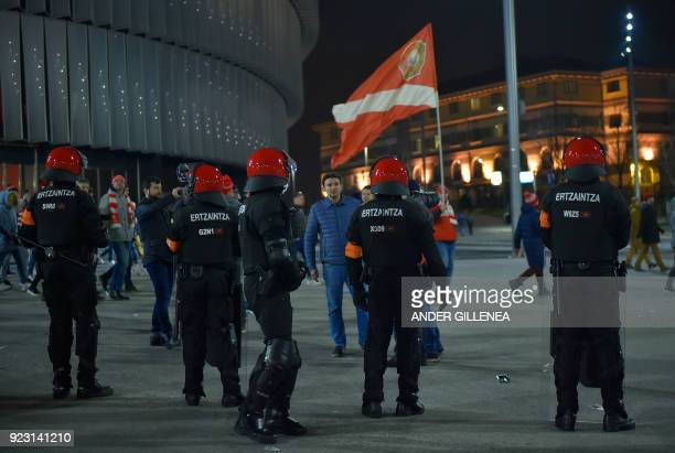 Spartak fans walk past Basque autonomous police officers outside the San Mames stadium after the Europa League Round of 32 second leg football match...