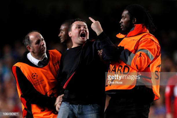 Spartak Moscow fan gestures to the home fans as he is led away after invading the pitch during the UEFA Champions League group F match between...