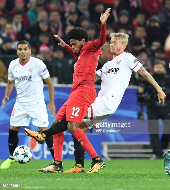 Spartak Moscow's forward from Brazil Luiz Adriano and Sevilla's defender from Denmark Simon Kjaer vie for the ball during the UEFA Champions League...