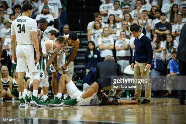 Spartans doctor Jeff Kovan attends to Spartans guard Miles Bridges after taking a hard fall during an exhibition college basketball game between...