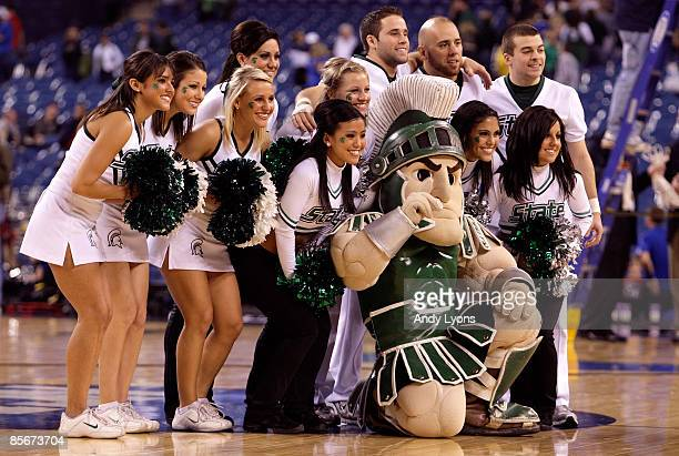 Sparty the mascot of the Michigan State Spartans poses for a photo with the cheerleaders against the Kansas Jayhawks during the third round of the...