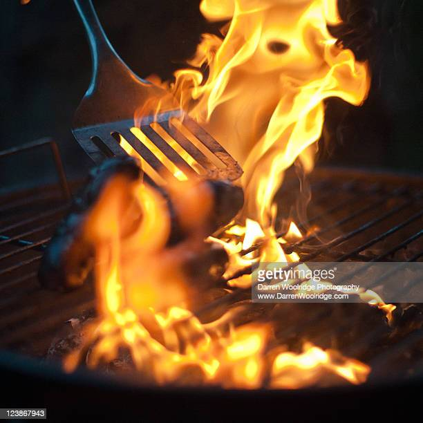 Spatula turning sausages in barbecue flames
