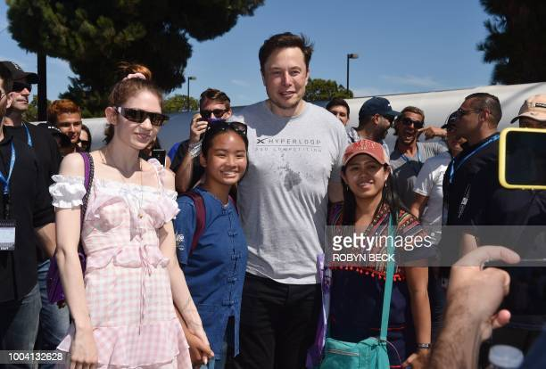 SpaxeX founder Elon Musk and Canadian musician Grimes pose for a snapshot with two attendees at the 2018 Space X Hyperloop Pod Competition in...