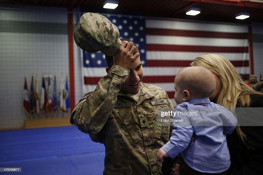Spc. Andrew Mendez of the U.S. Army's 3rd Brigade Combat Team, 1st Infantry Division, reacts upon seeing his five month-old son Elliot Mendez following a homecoming ceremony in the Natcher Physical Fitness Center on Fort Knox on February 27, 2014 in Fort Knox, Kentucky. About 100 soldiers returned to Fort Knox after a nine-month combat deployment conducting village stability operations and working alongside Afghan military and police forces.
