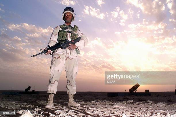 Spc Bobby Jenkin scans the surrounding area at sunset maintaining security for a Patriot missile battery February 15 2003 at Al Udeid Air Base near...