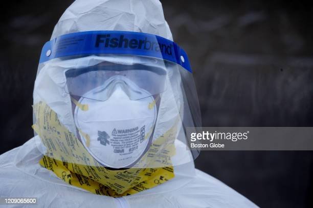Spc. Brandon Bessette of the Rhode Island Army National Guard dresses in personal protection equipment while preparing to perform a medical swab...