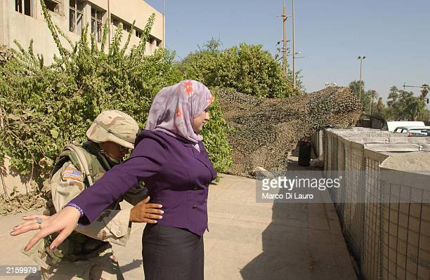 S Spc Johanna Landry from New York a medic attached to the Alfa Company 26 Infantry searches a woman while on guard at the gate of Saddam Hussein's...