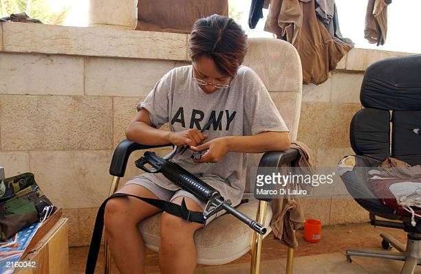 S Spc Johanna Landry from New York a medic attached to the Alfa Company 26 Infantry cleans her M16 rifle in her barrack in Saddam Hussein's...