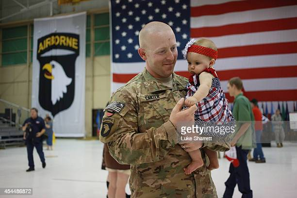 Spc. Josh Carter of the U.S. Army's 159th Combat Aviation Brigade, 101st Airborne Division, holds his niece, six-month-old Addaline Carter, following...