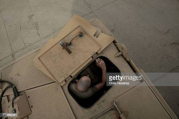 Spc Travis Nelson of Bridge City Texas in a maintenence company in the US Army's 212 infantry sprays lubricant on the hatch of a new MRAP vehicle...