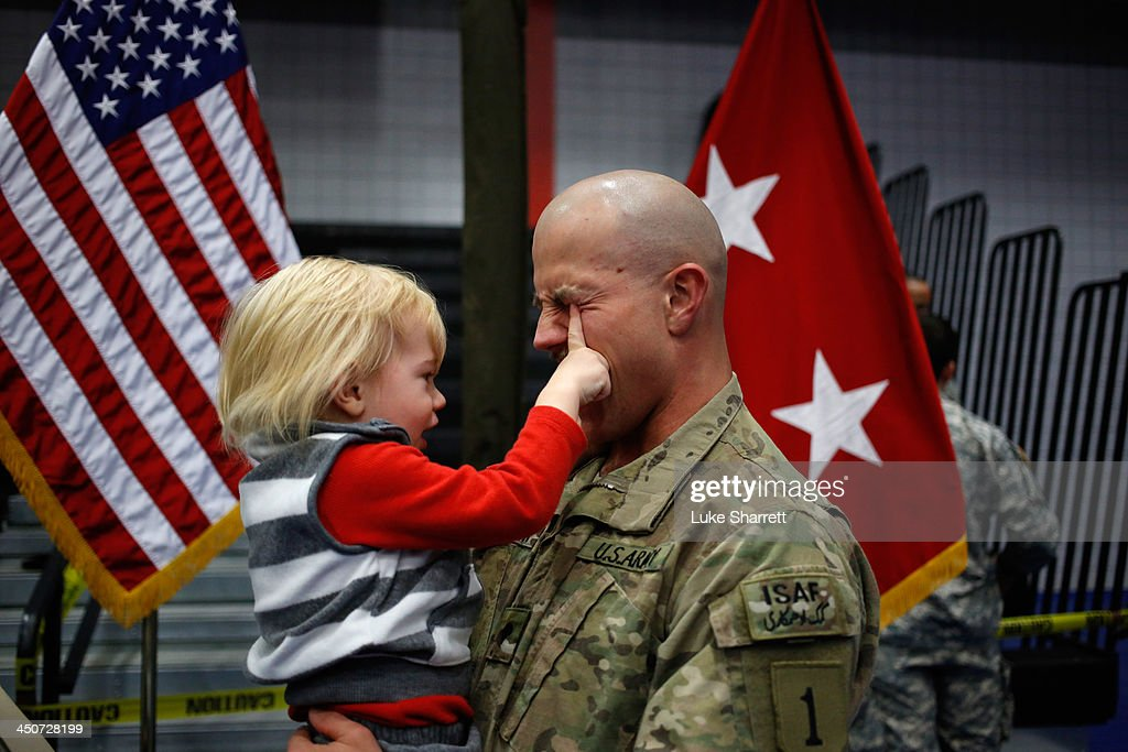 Spc. Troy Harrison of the U.S. Army's 3rd Brigade Combat Team, 1st Infantry Division, holds his 2-year-old son, Avery Harrison during a homecoming ceremony in the Natcher Physical Fitness Center on Fort Knox in the early morning hours of Wednesday, November 20, 2013 in Fort Knox, Ky. The 250 soldiers returned to Fort Knox after a nine-month combat deployment working alongside Afghan military and police forces in Afghanistan's Zabul Province.