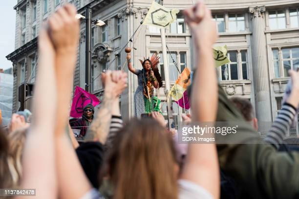 A speaker from Brazil is seen standing on the Extinction Rebellion pink boat stage to addressing a speech to the crowd during the Extinction...
