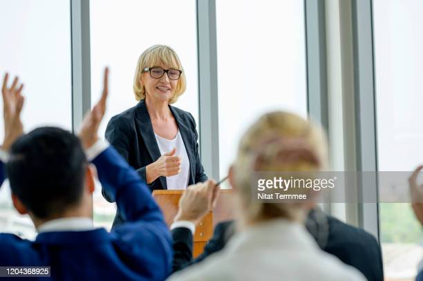 speaker giving a talk on corporate business conference or business seminar while group of business people hear speaker give conference speech . - press conference stock pictures, royalty-free photos & images