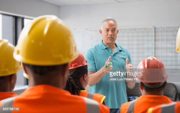 speaker giving presentation to construction workers - safety stock pictures, royalty-free photos & images
