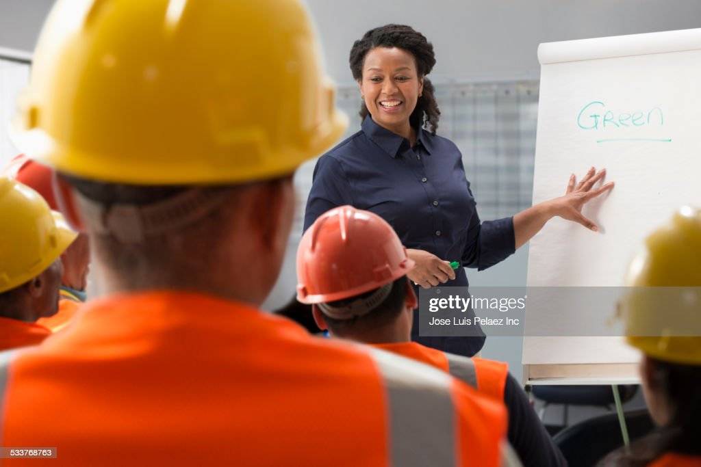 Speaker giving presentation to construction workers : Stock Photo