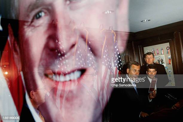 Speaker of the House John Boehner is reflected in a framed photograph of former President George W Bush during a news conference at the Republican...