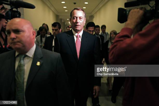 Speaker of the House John Boehner is surrounded by reporters staff and security after a news conference at the US Capitol August 1 2011 in Washington...