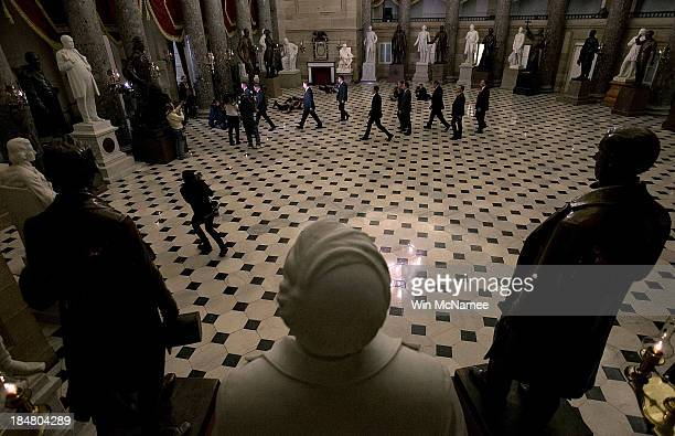 Speaker of the House John Boehner walks with an entourage through Statuary Hall for a vote in the House of Representatives to end the government...