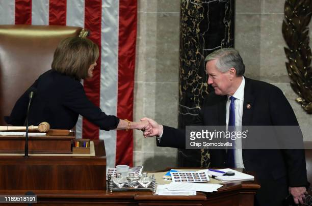 Speaker of the House Nancy Pelosi and Rep Mark Meadows shake hands as the House of Representatives votes on the second article of impeachment of US...