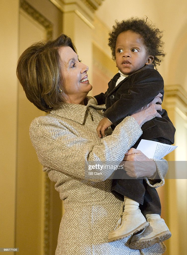 Speaker of the House Nancy Pelosi, D-Calif., surrounded by families with chhildren, makes a brief statement about the expected passage of SCHIP legislation later in the day on Wednesday, Feb. 4, 2009. Speaker Pelosi is shown holding Jacob Hodges, 16 months.