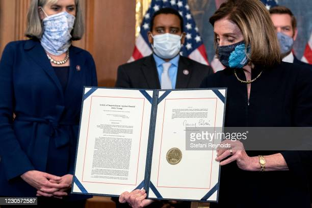 Speaker of the House Nancy Pelosi displays a signed an article of impeachment against President Donald Trump at the U.S. Capitol on January 13, 2021...